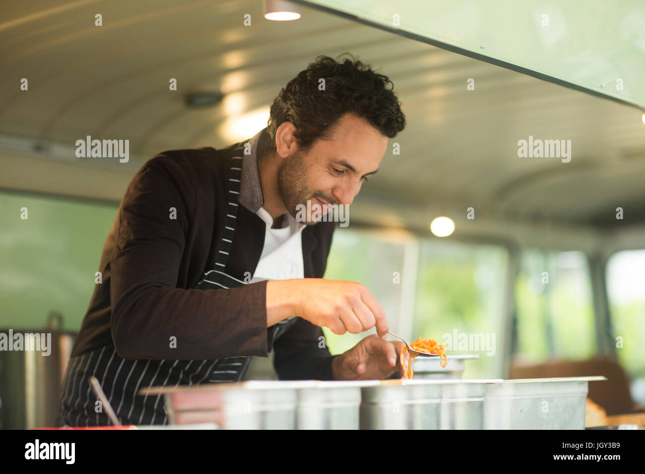 Small business owner serving food from van food stall hatch - Stock Image