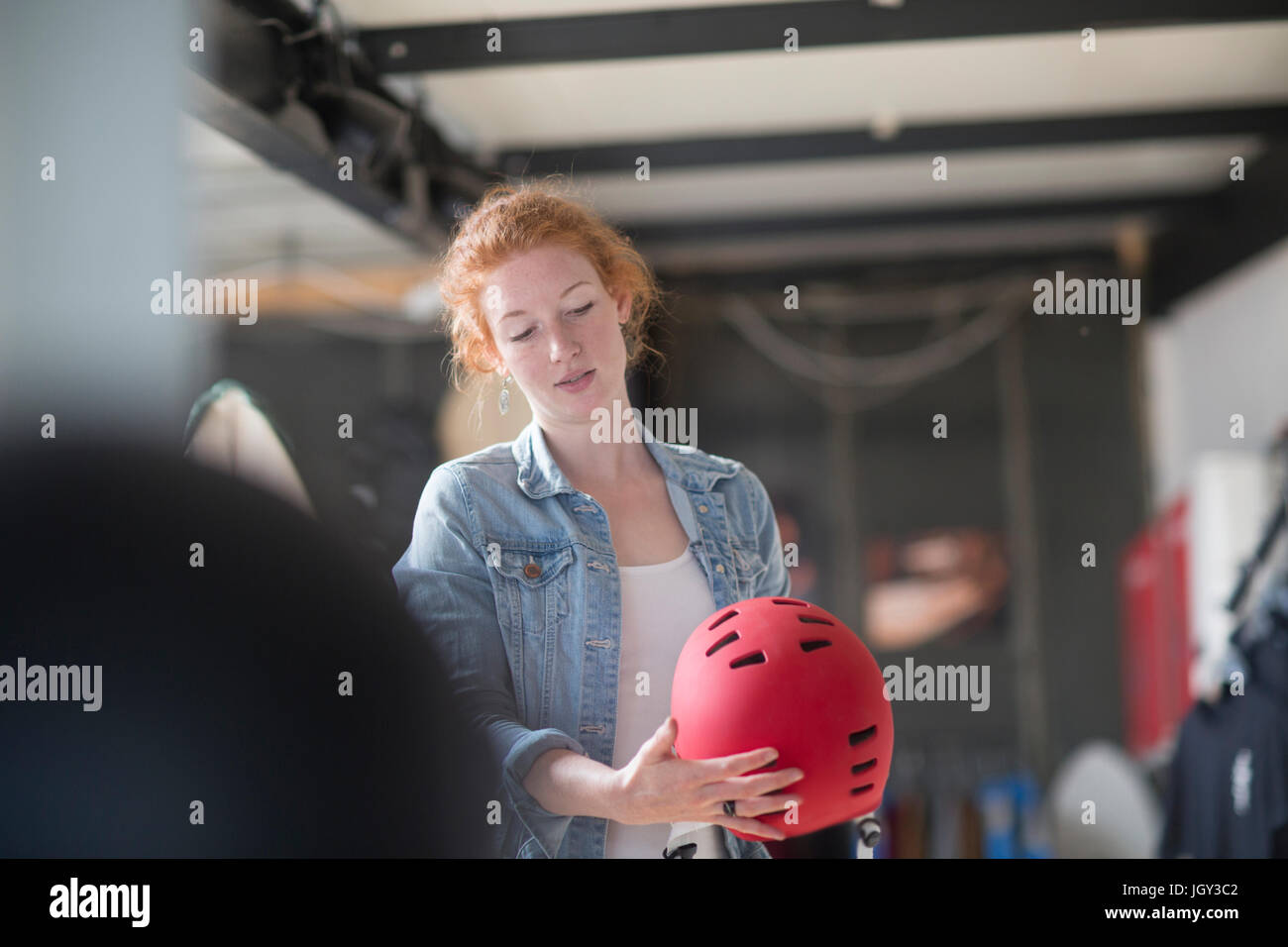 Woman working in board shop, inspecting safety helmet - Stock Image