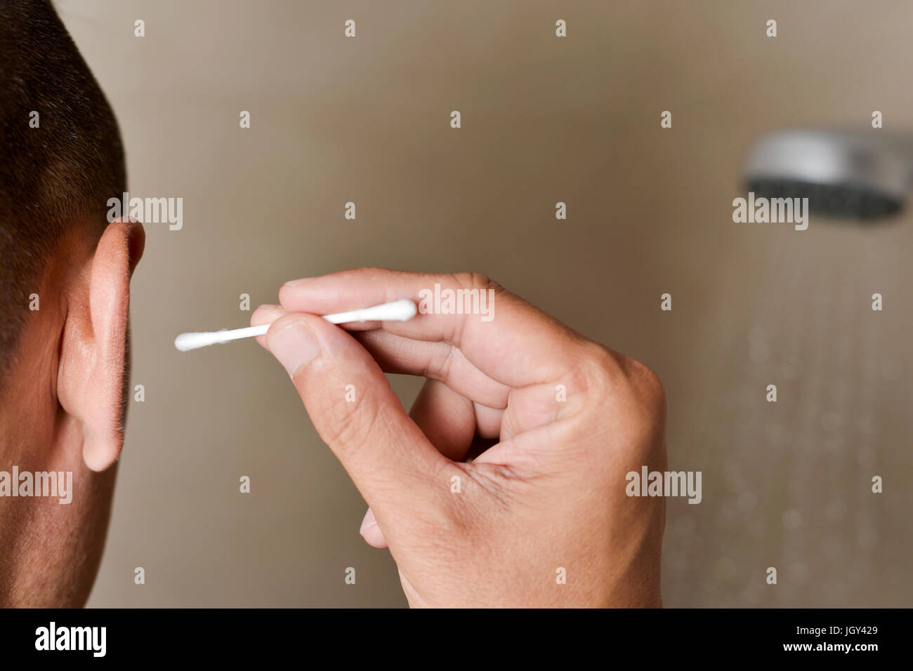 closeup of a young caucasian young man in the bathroom seen from behind about to clean his right ear with a cotton - Stock Image