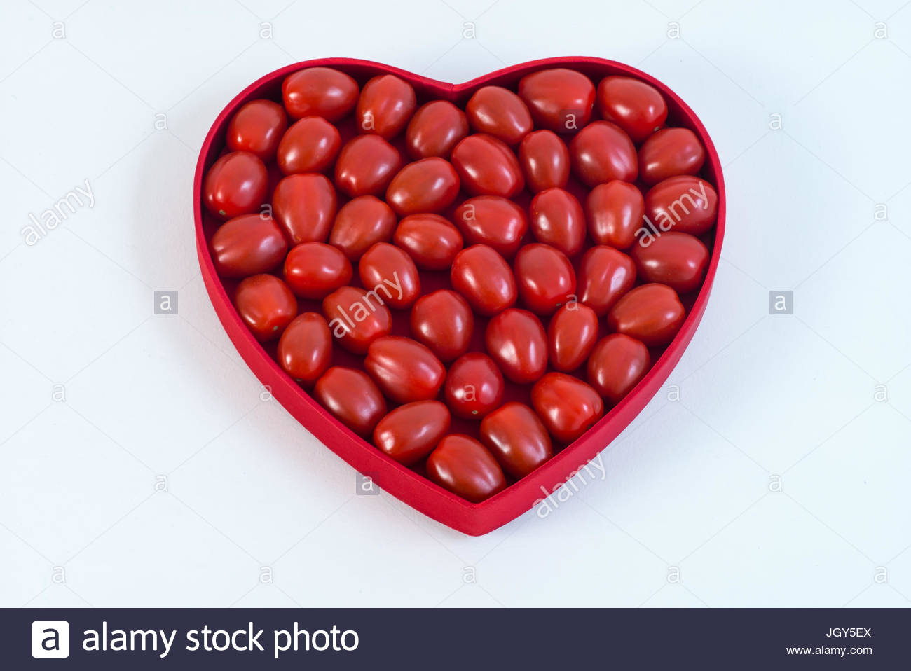 Cherry tomatoes in heart shaped plate against white background Stock Photo
