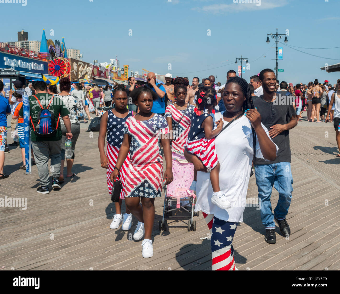 A patriotically dressed family promenades on the boardwalk in Coney Island in Brooklyn in New York  on Independence - Stock Image