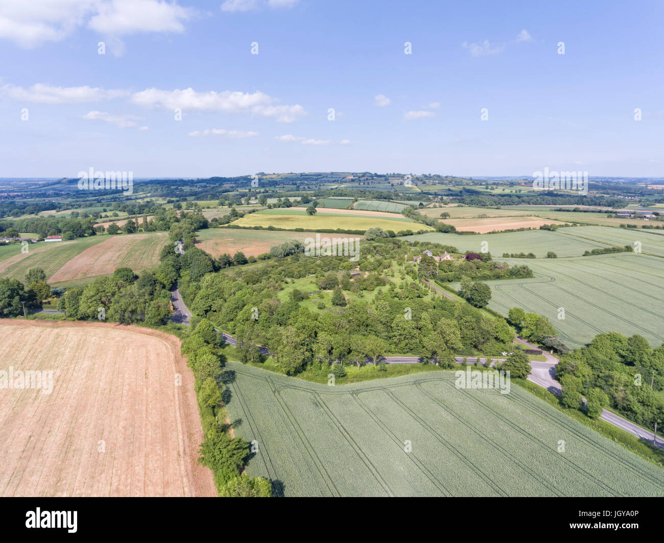 Aerial view of agriculture farm land with green wheat and ploughed fields, small village, in an English rural countryside, - Stock Image