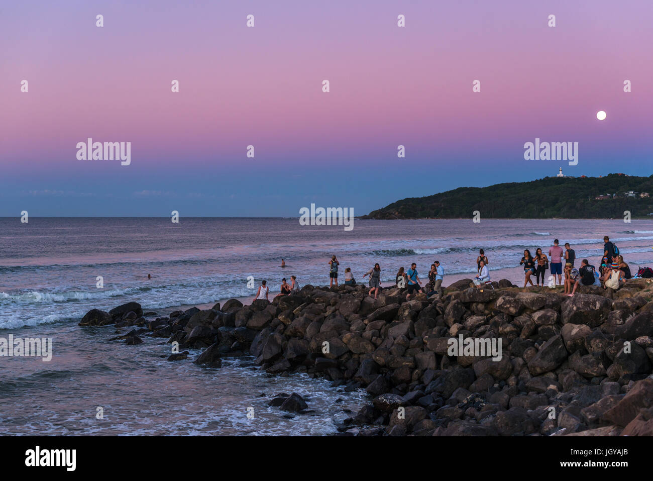 People watch the sun set and full moon rise at Byron bay, New South Wales, Australia. - Stock Image