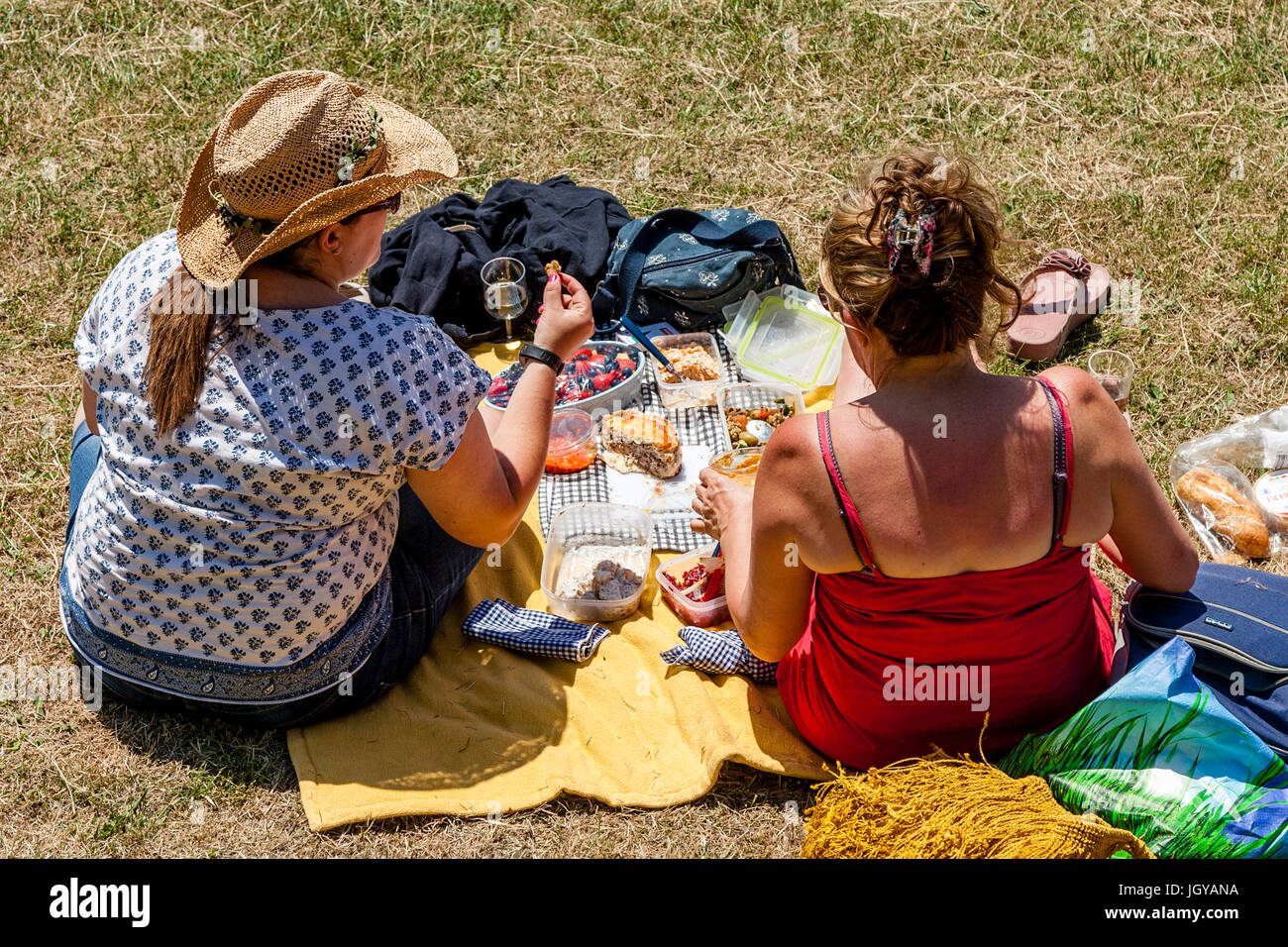 Two Women Sitting On The Banks Of The River Ouse Enjoying A Picnic, Lewes, Sussex, UK - Stock Image