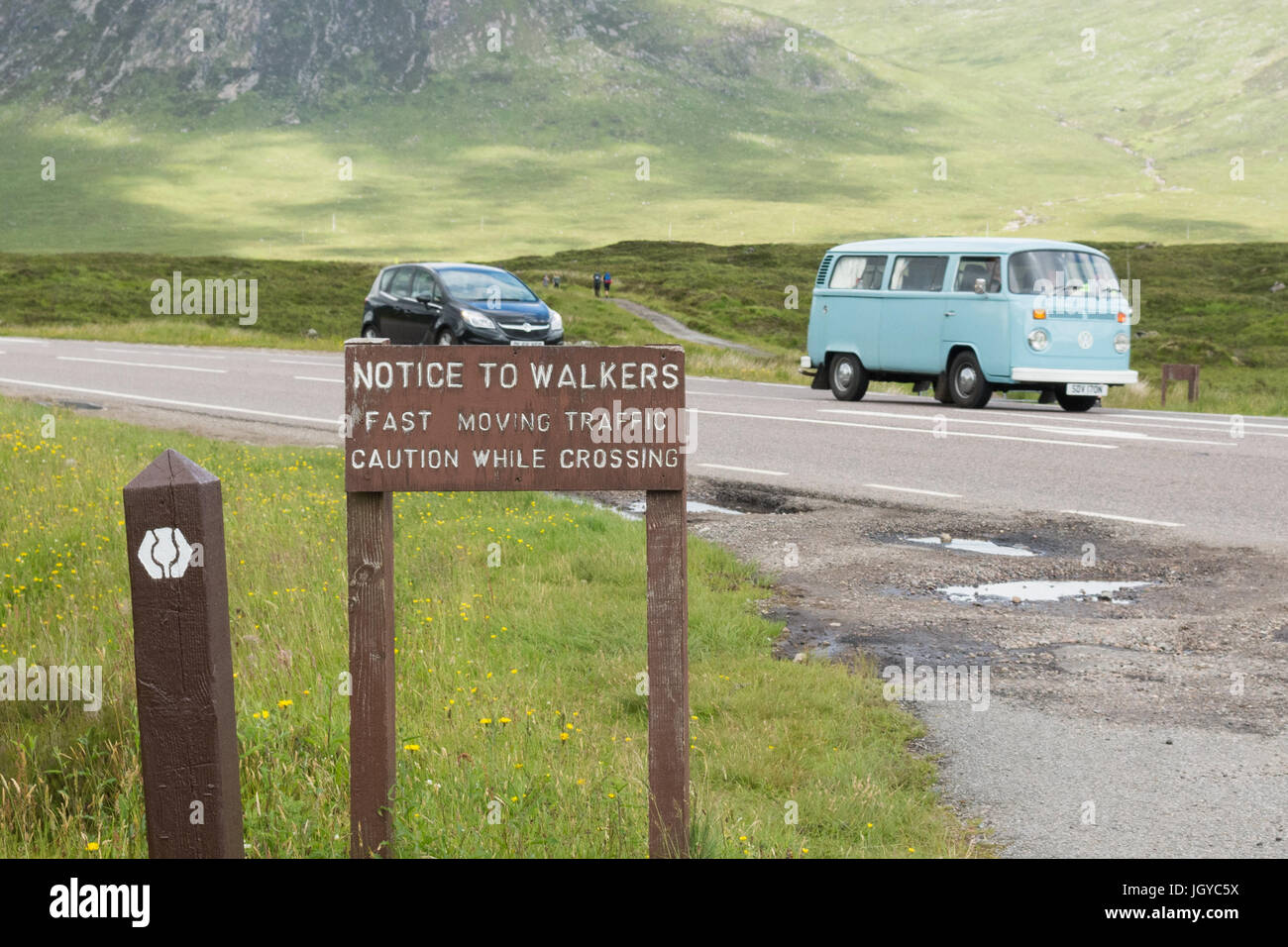 Sign warning West Highland Way walkers to beware of traffic on A82 in Glencoe, Scotland, UK - Stock Image