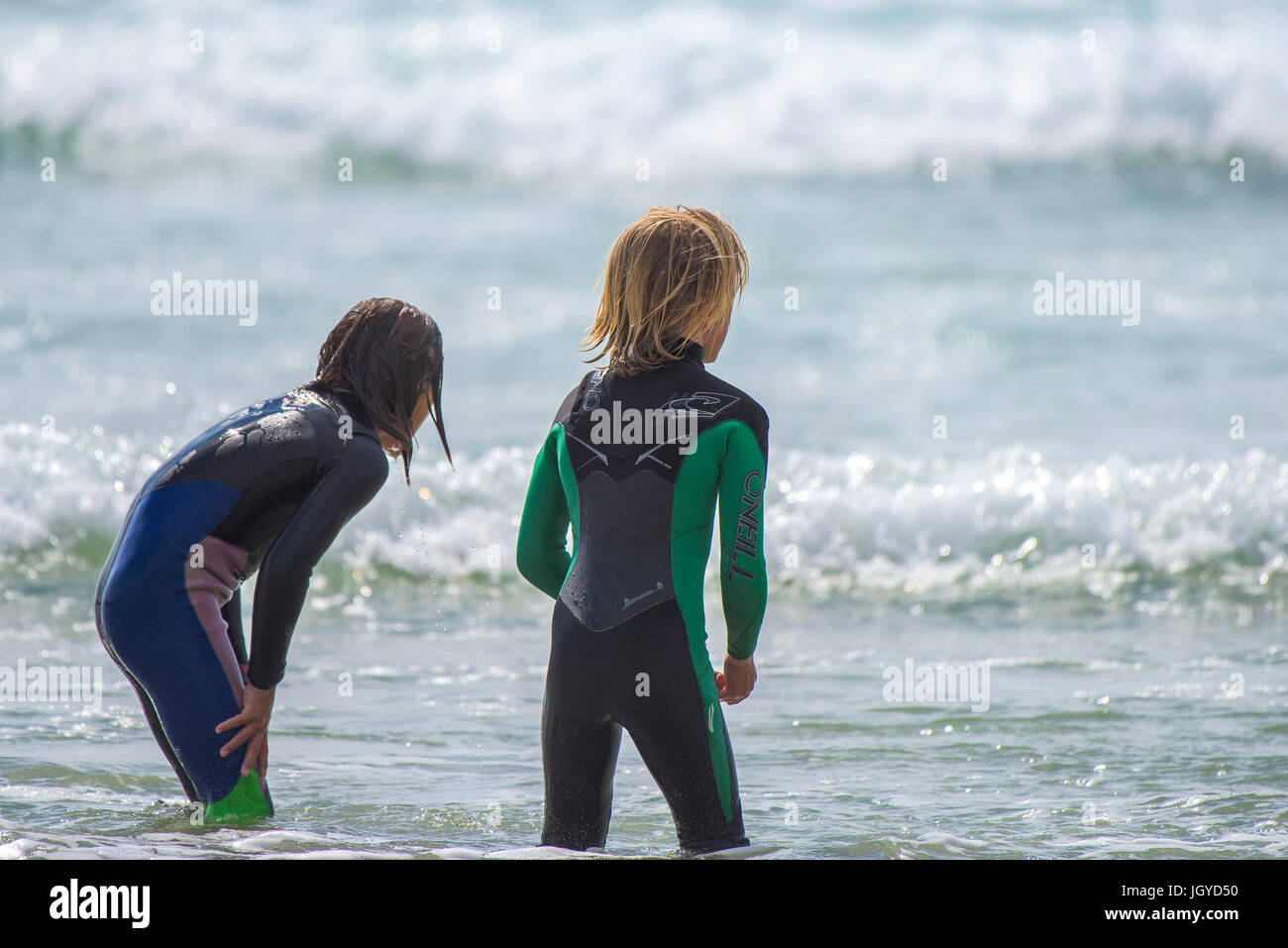 Two young boys wearing wetsuits playing together in the sea. - Stock Image