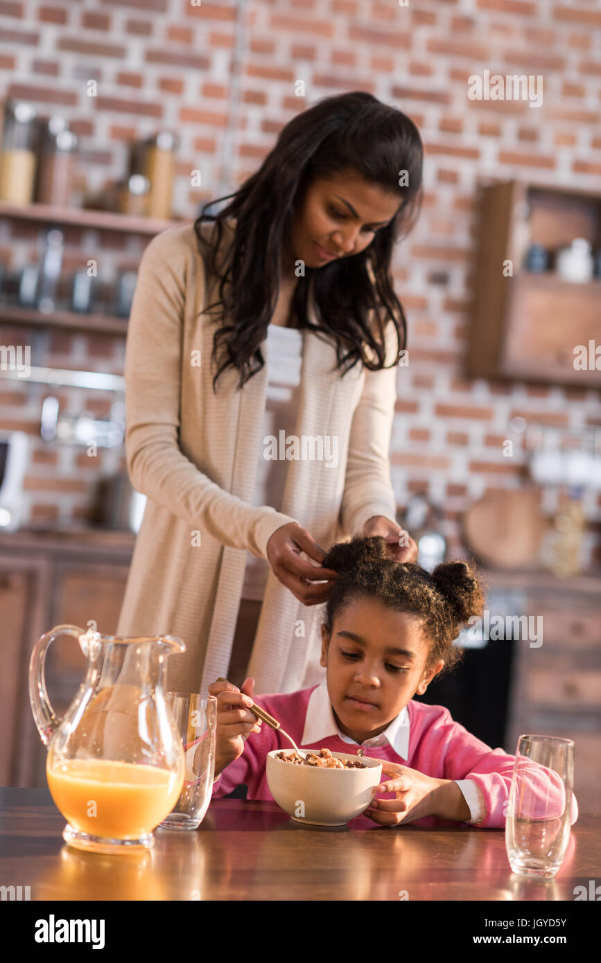 mother doing hairstyle to little girl during breakfast at home - Stock Image