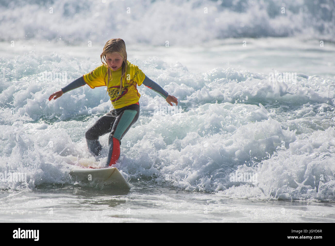 Surfing UK. Surfing child wave. An eight year old surfer competing in the UK Schools Surf Championship. - Stock Image