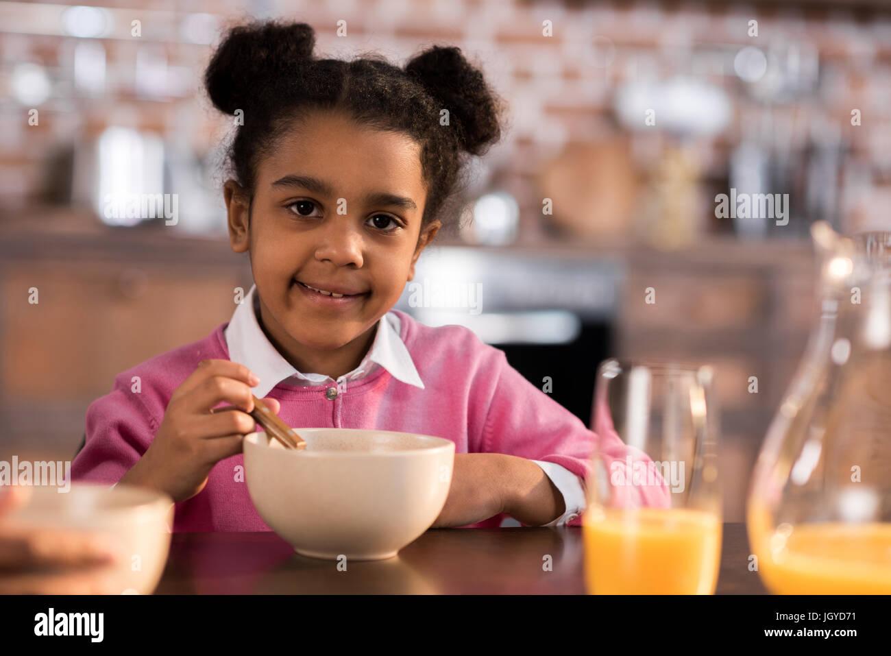 portrait of smiling little girl having breakfast at home - Stock Image