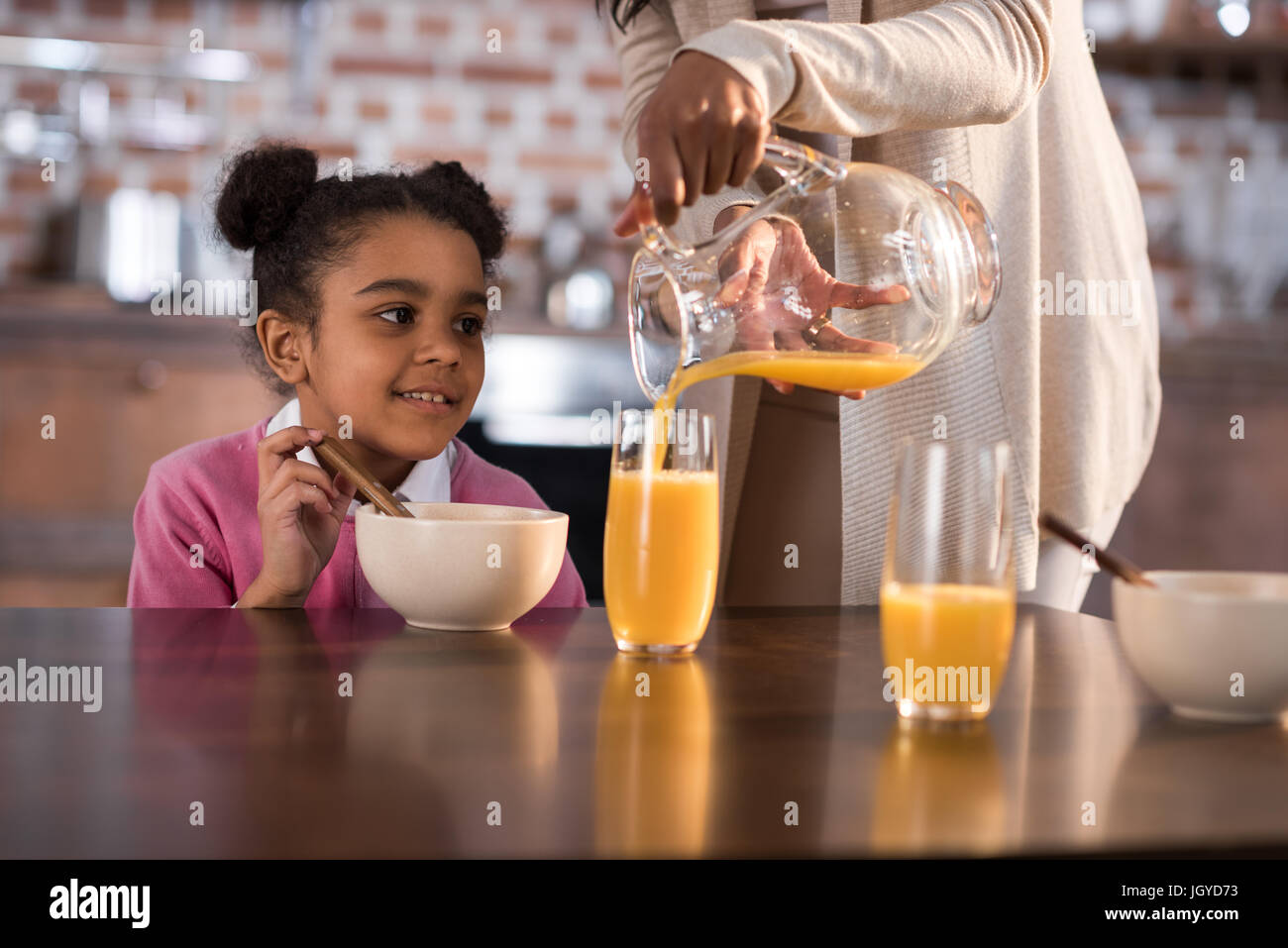 mother pouring juice into daughter's glass during breakfast at home - Stock Image