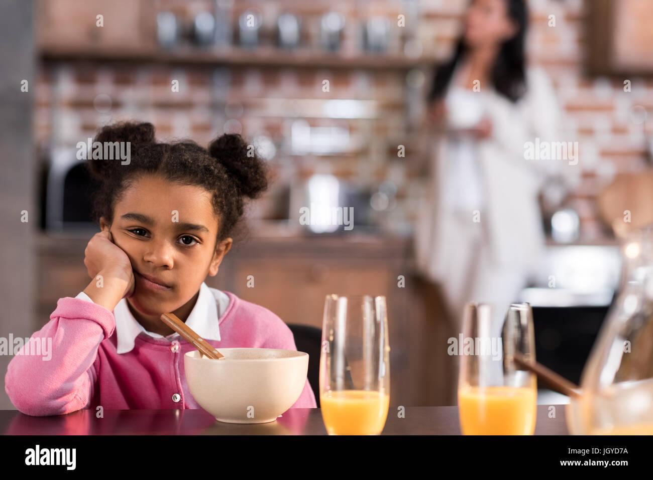 portrait of upset little girl having breakfast at home - Stock Image