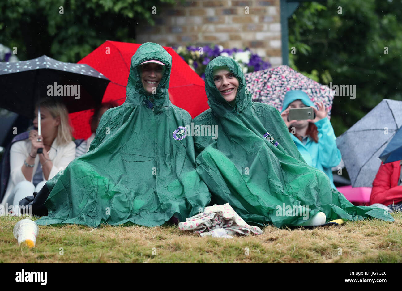 Spectators in ponchos shelter from the rain on Murray Mound on day eight of the Wimbledon Championships at The All - Stock Image