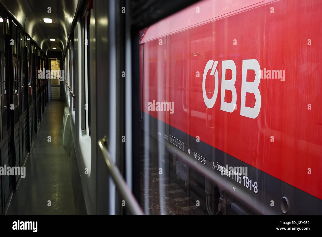 OBB, the logo of the Austrian Federal Railways, on the side of a train seen from another train. - Stock Image
