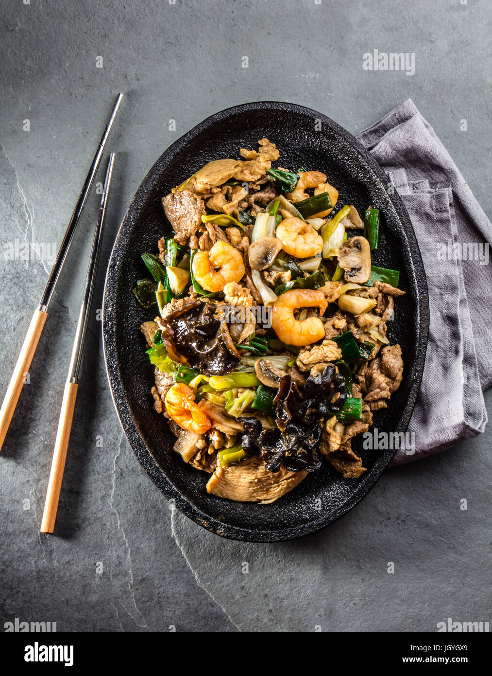 Chinese food. Te pam sao. Pan of fried beef, pork, chicken, shrimps, shiitake mushroom, champions and spring onion. - Stock Image