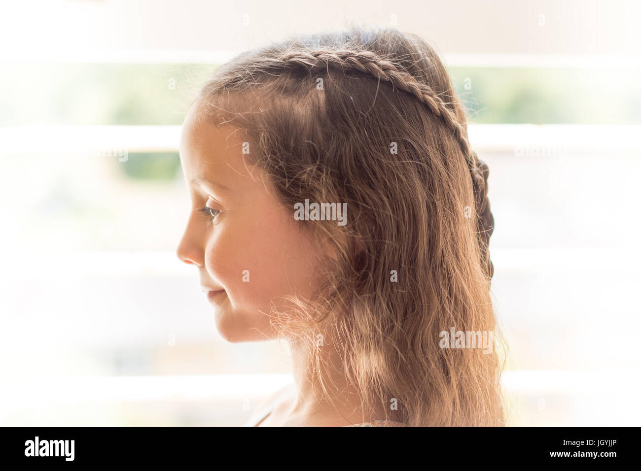 High-key portrait of girl with braided hair. Child with long brown with hairstyle with plaits, in front of window - Stock Image