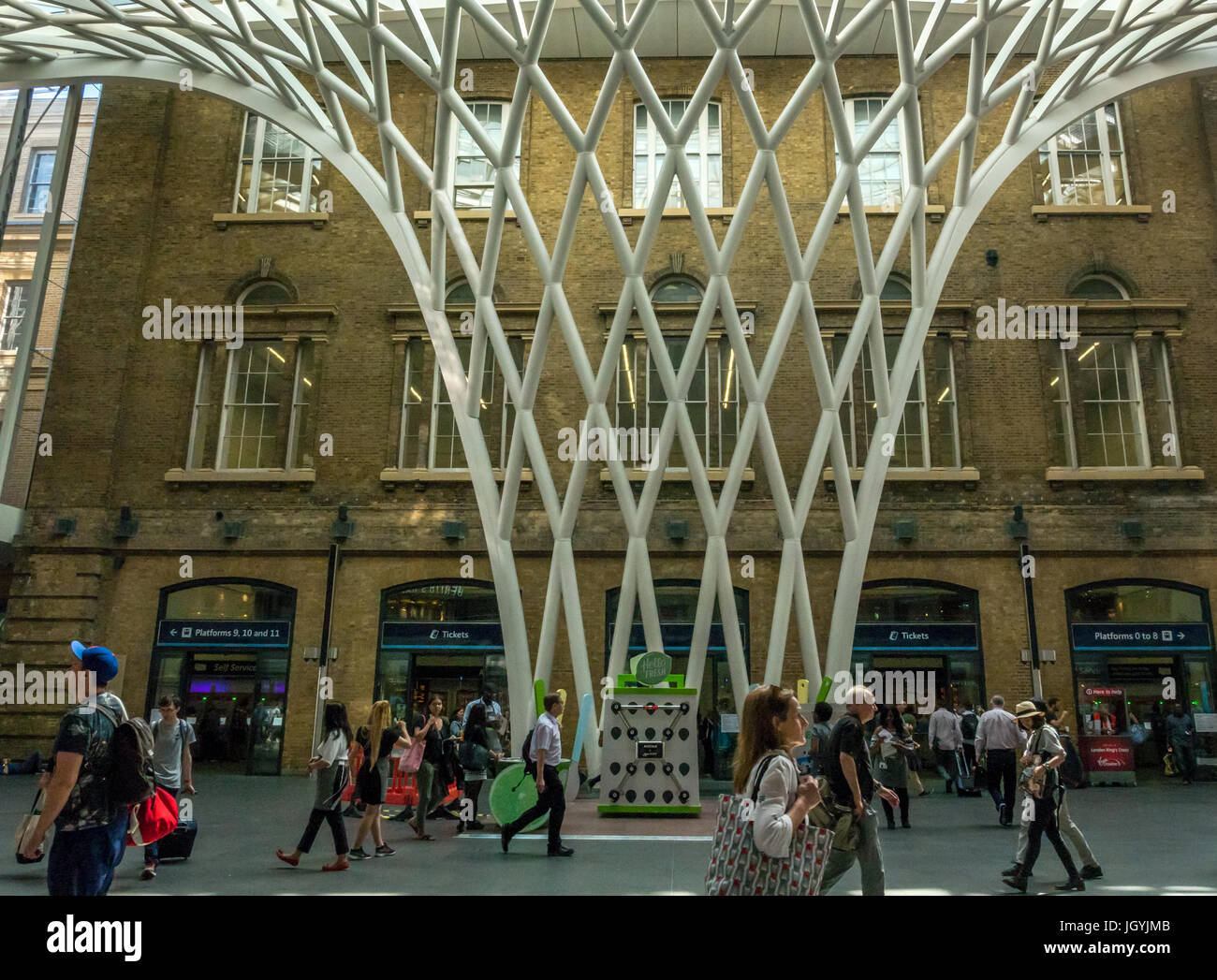 People in main concourse at King's Cross Station, London, England,  UK, in front of giant arched lattice trellis - Stock Image