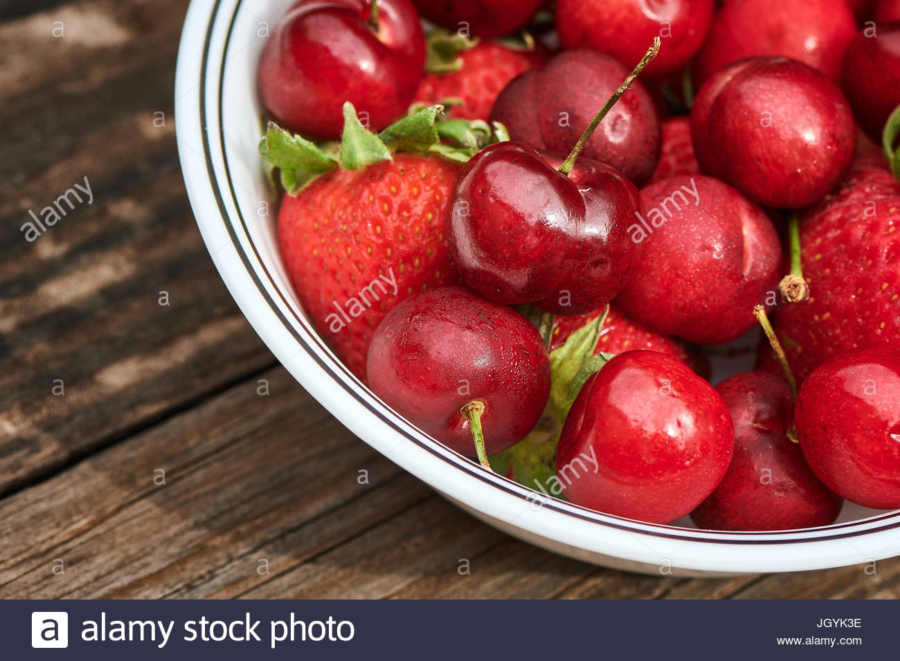 Bowl of fresh organic strawberries and cherries on a vintage wood table - Stock Image