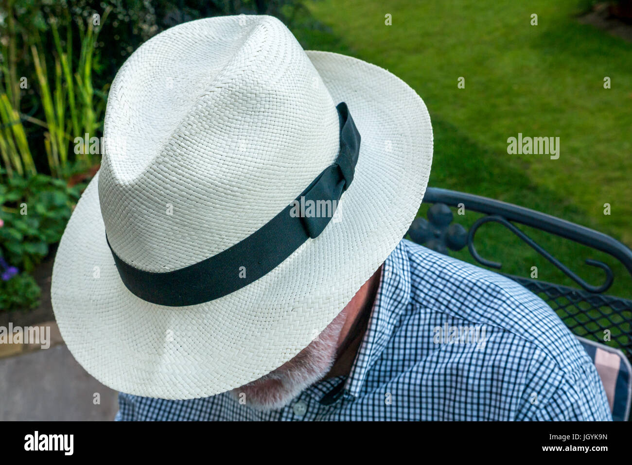fd483bce748878 Close up of older man with white beard sitting outside in garden wearing a  Panama hat