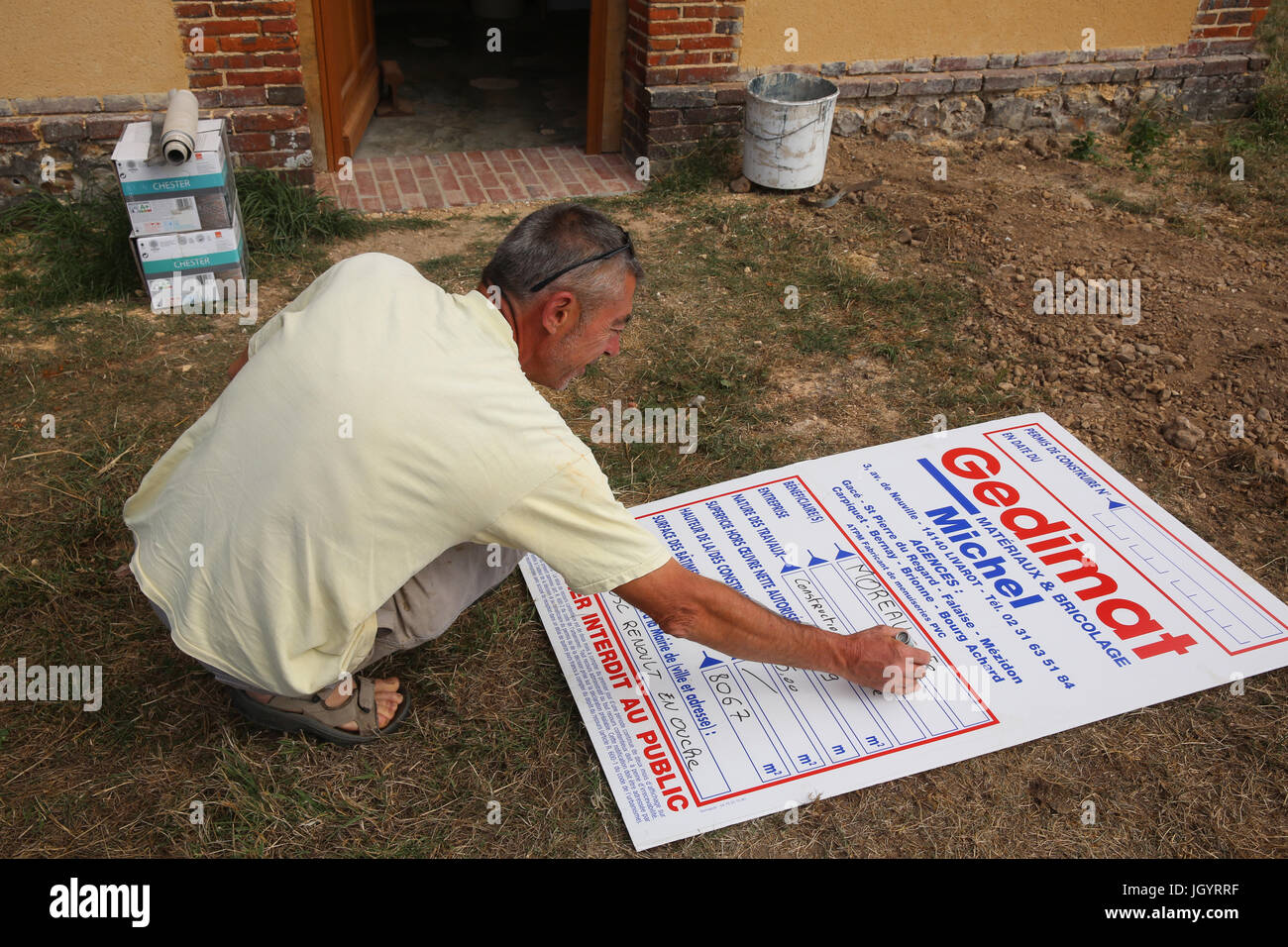 Man filling a notice sign. France. - Stock Image