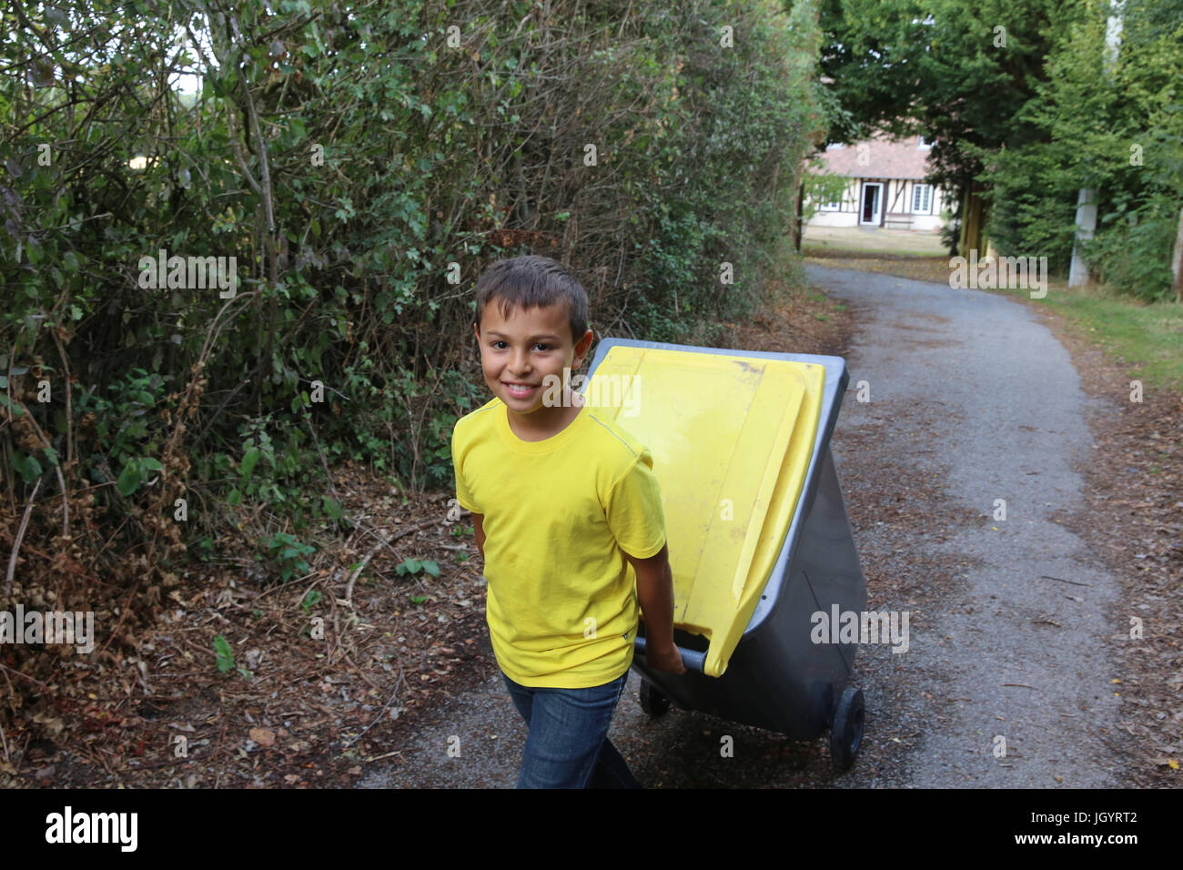 Boy pulling a recycling trash can. France. - Stock Image