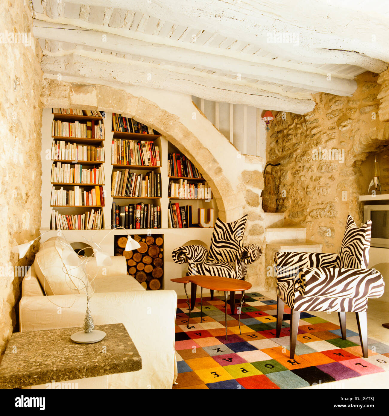 Zebra armchairs in a rustic living room - Stock Image