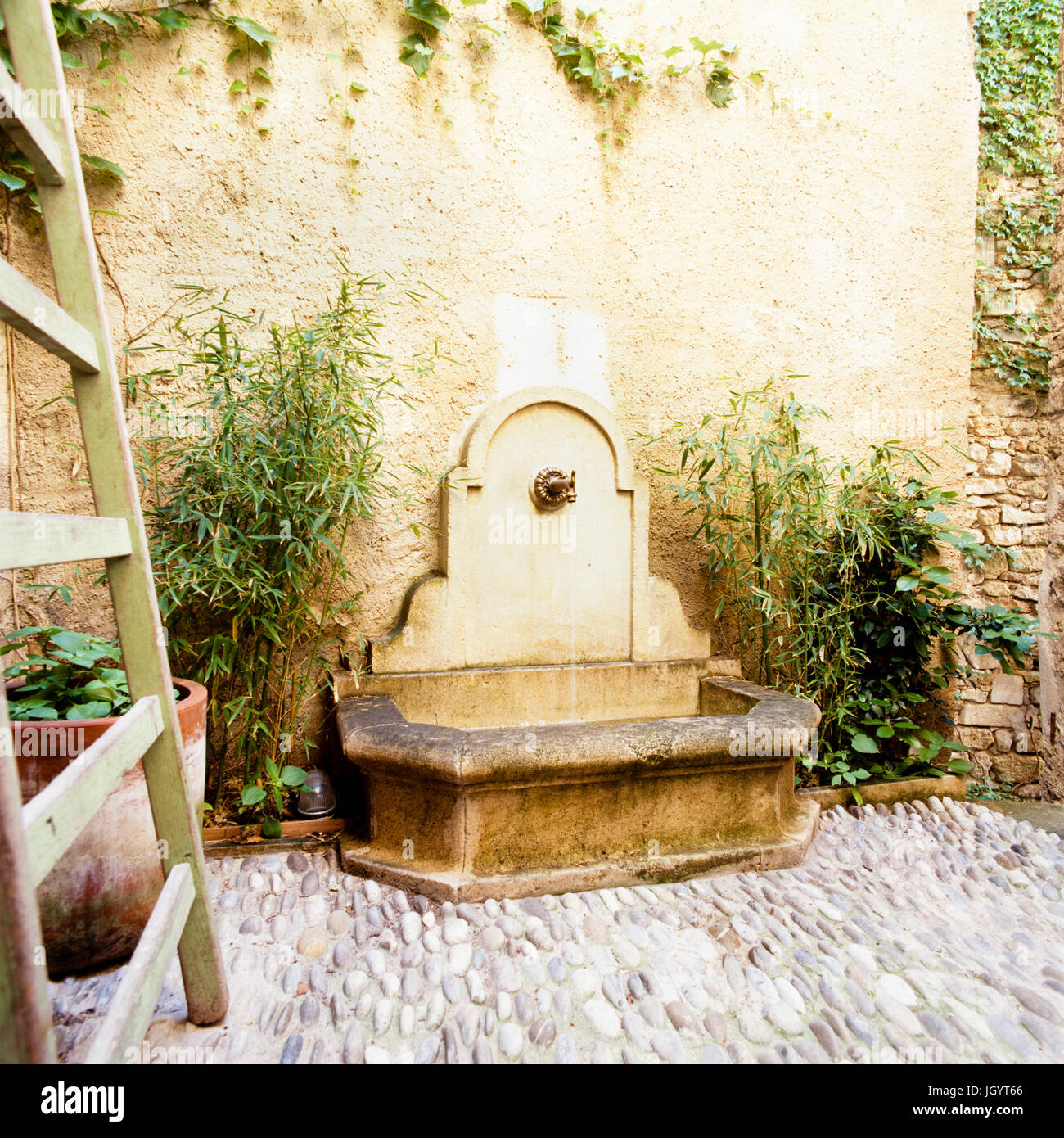 Water fountain on a cobblestone patio - Stock Image