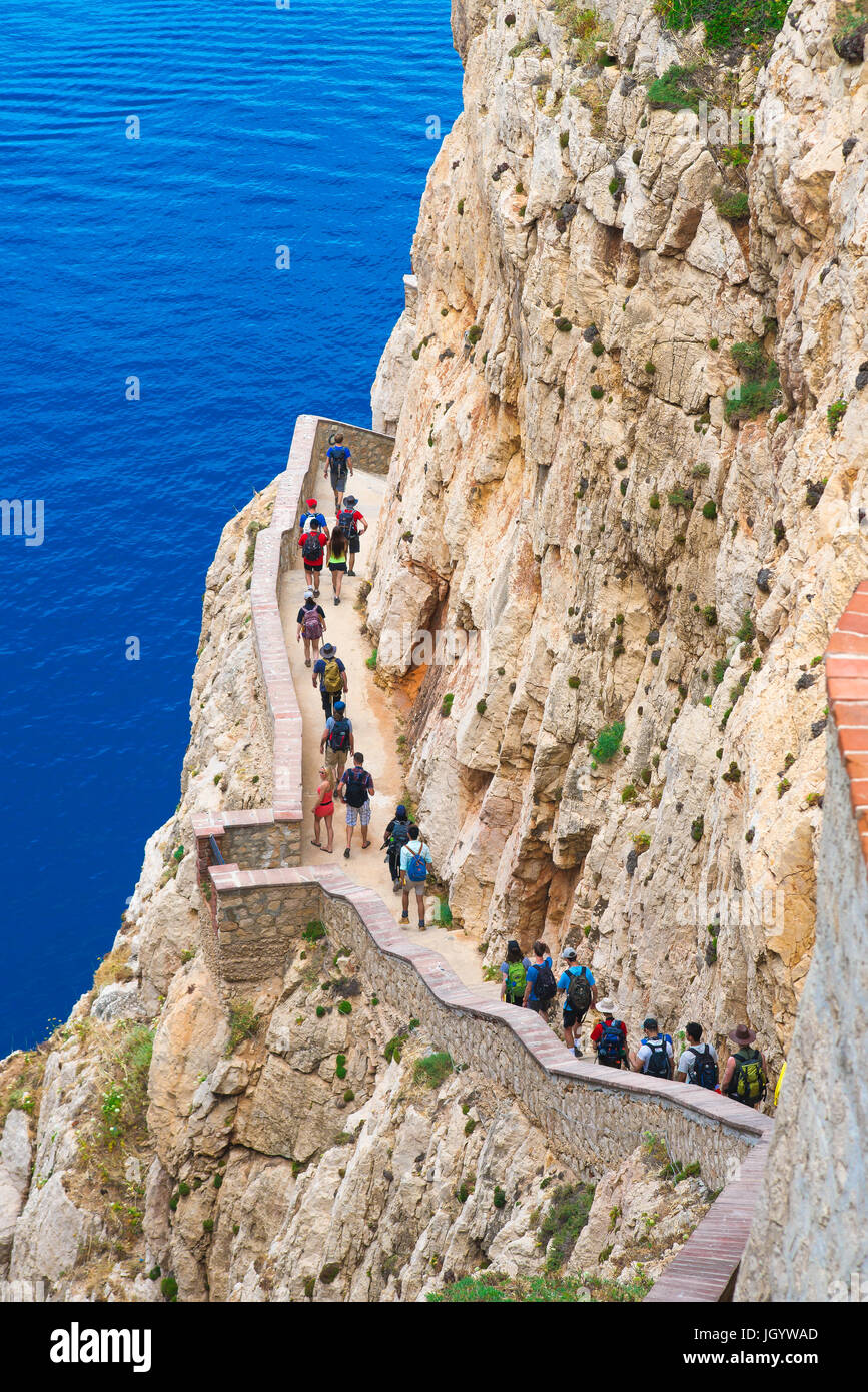 Sardinia tourism, tourists head for the entrance to the Grotta di Nettuno near Alghero by way of the 654 step cliff - Stock Image