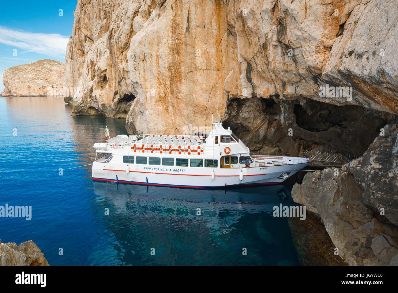 Grotta di Nettuno Sardinia, a tour boat is moored in the entrance to Grotta di Nettuno below Capo Caccia, near Alghero, - Stock Image