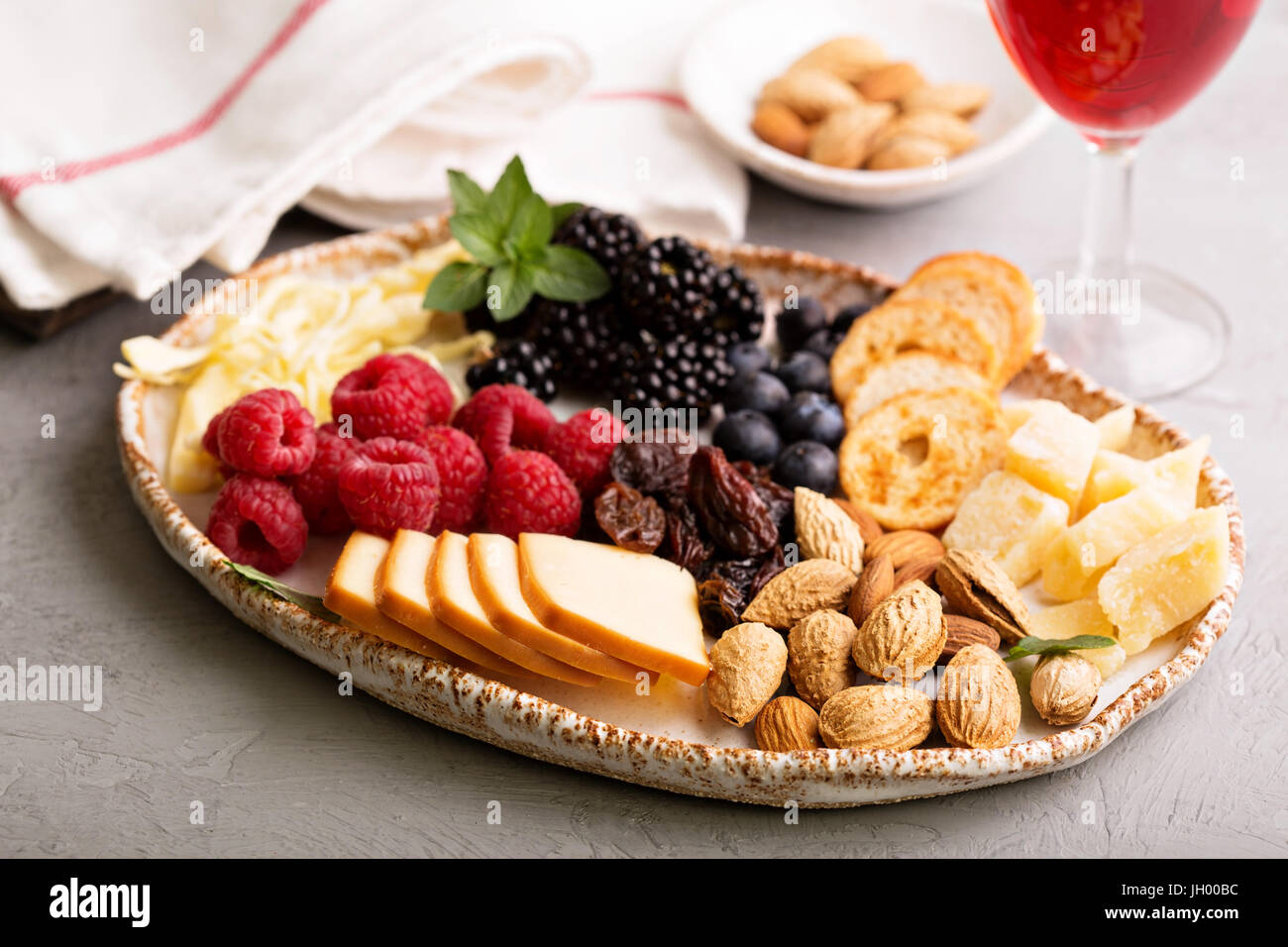 Cheese plate with nuts and berries - Stock Image