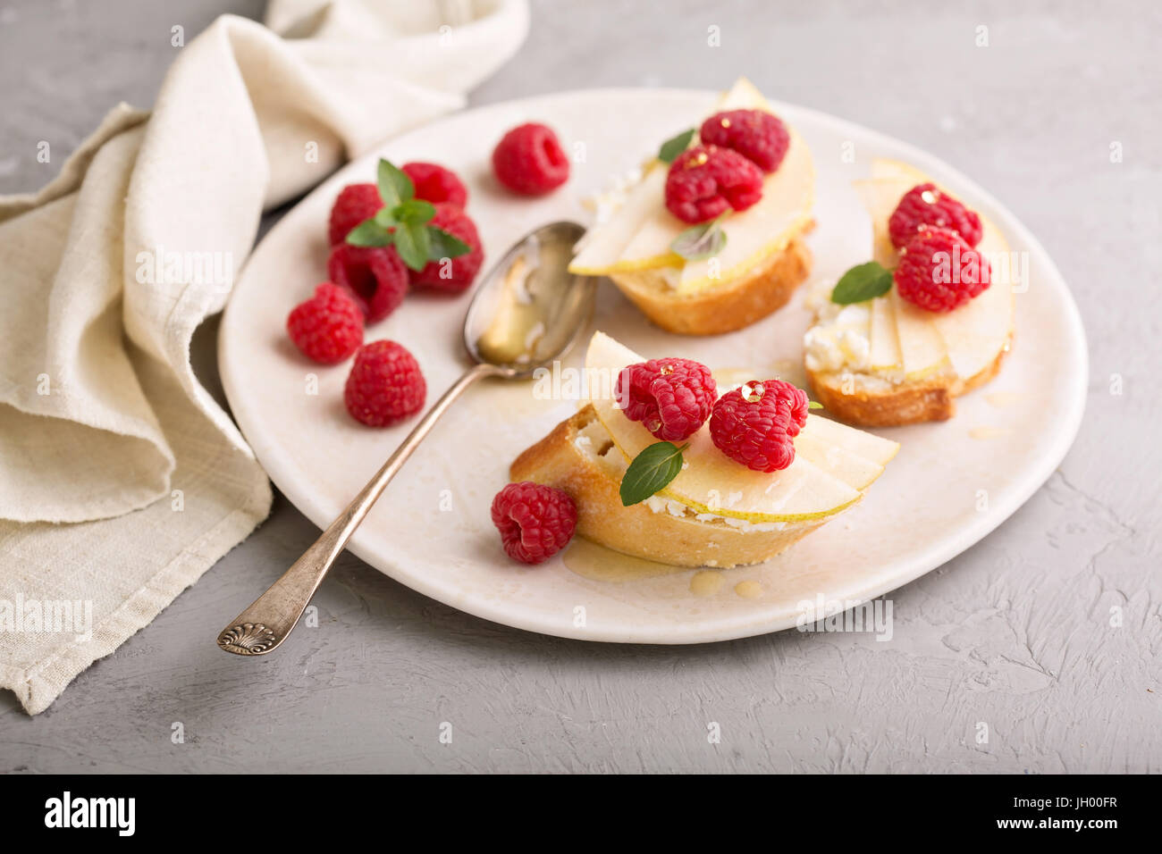 Open faced sandwiches with cheese, pears and raspberry - Stock Image