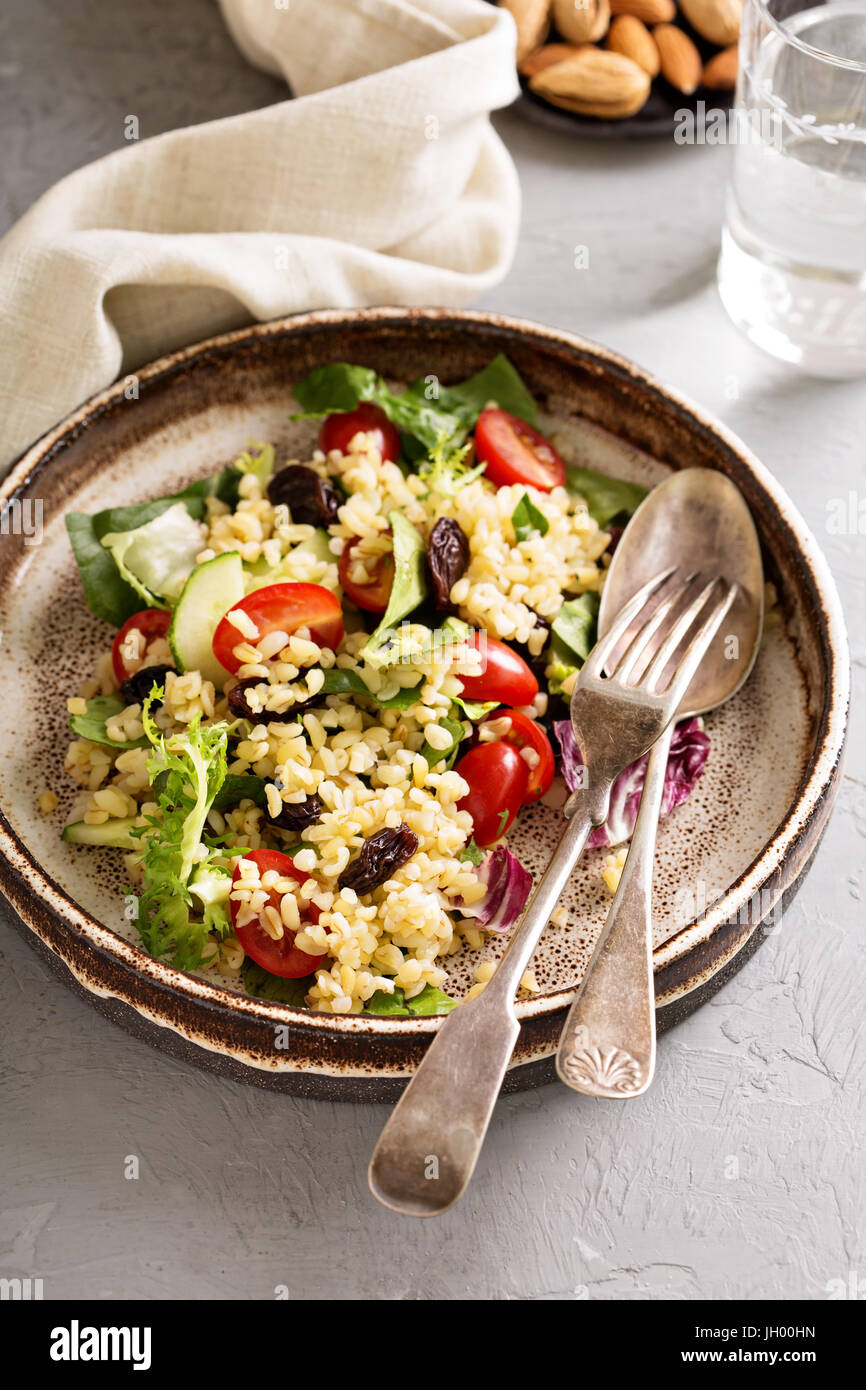 Warm salad with bulgur, vegetables and leaves - Stock Image