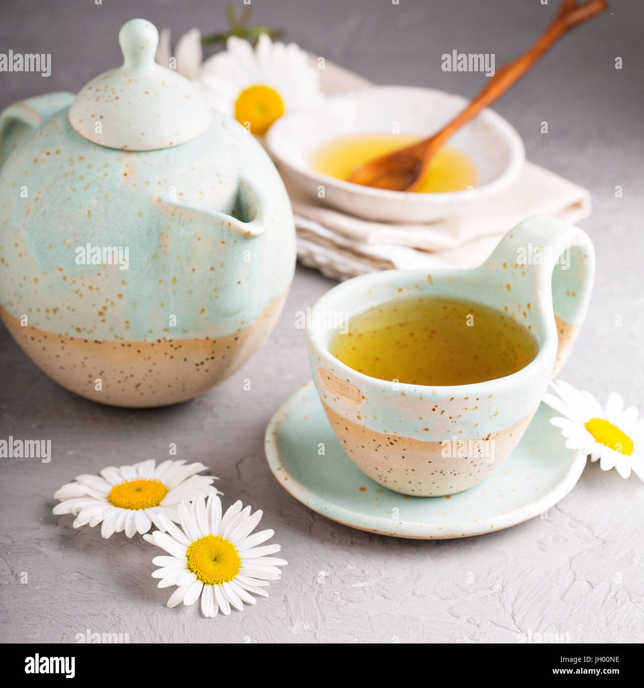 Camomille tea in handmade ceramic cup - Stock Image