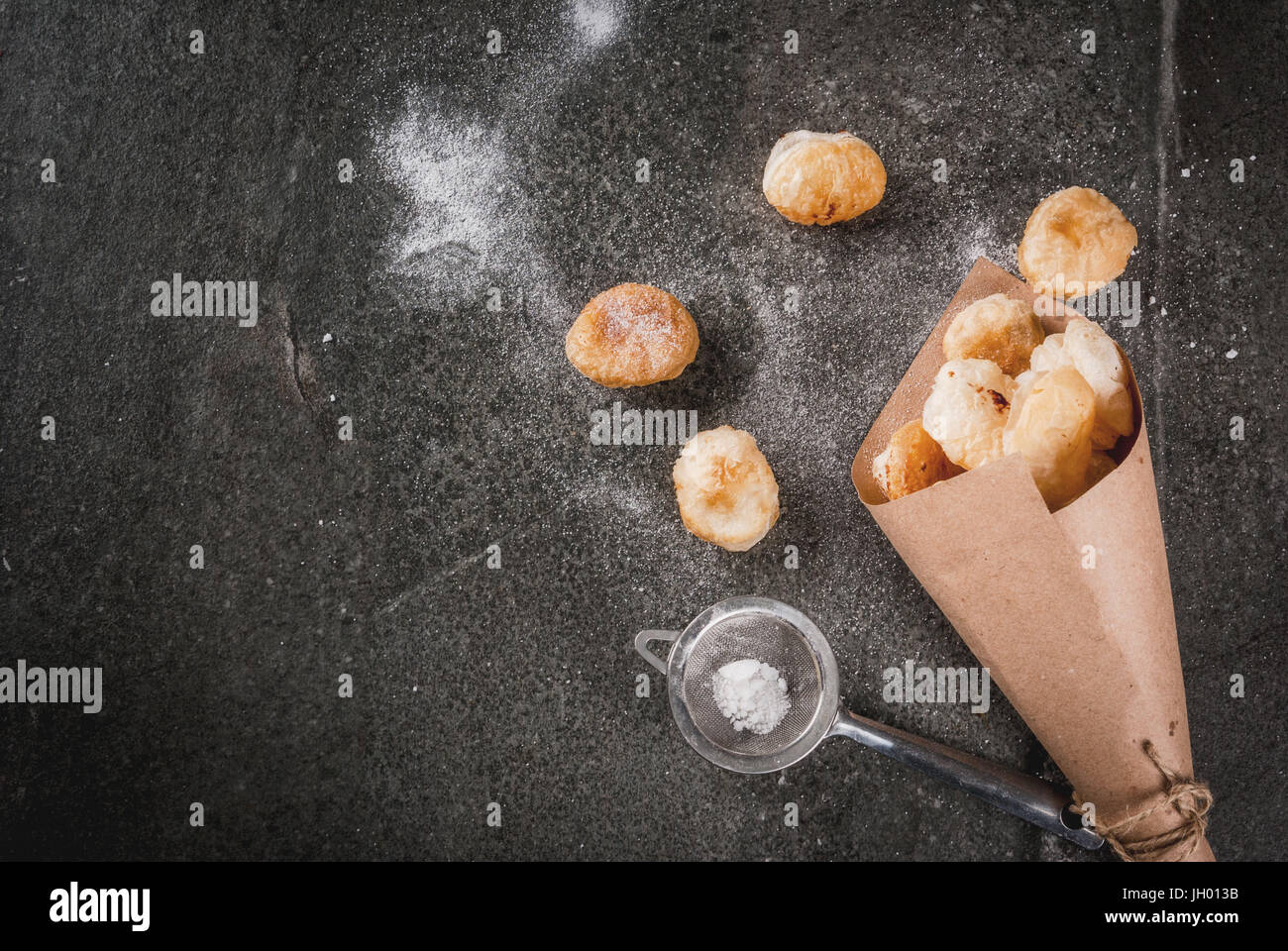 Homemade baking, puff pastries. Trendy food. Cronuts popcorn, puff donuts holes, in paper bag, with powdered sugar. - Stock Image