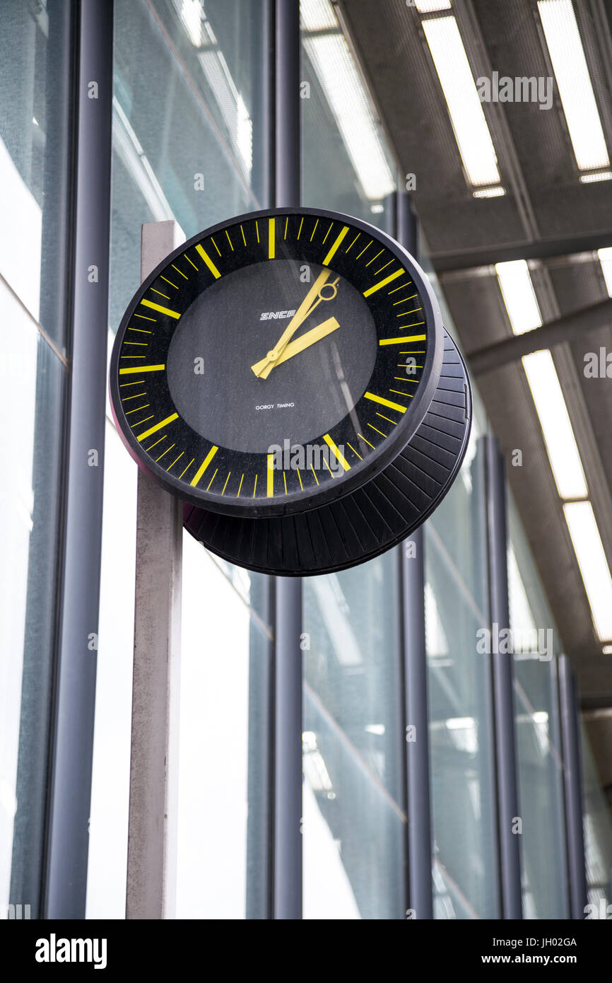 A black clock with yellow details hanging from a modern building - Stock Image