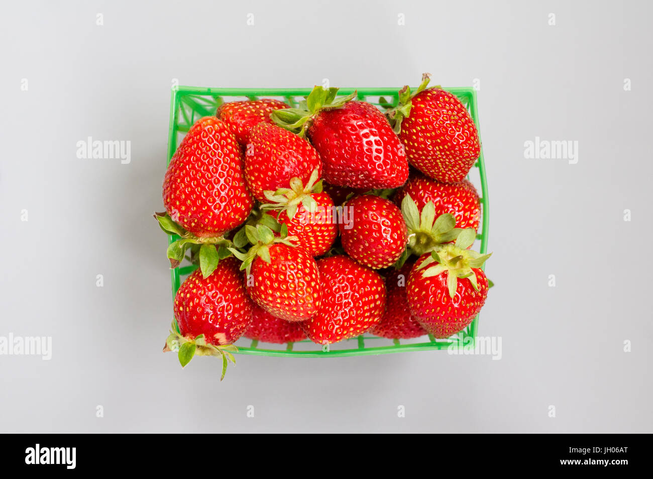 Fresh strawberries in a plastic green punnet on a light grey background - Stock Image