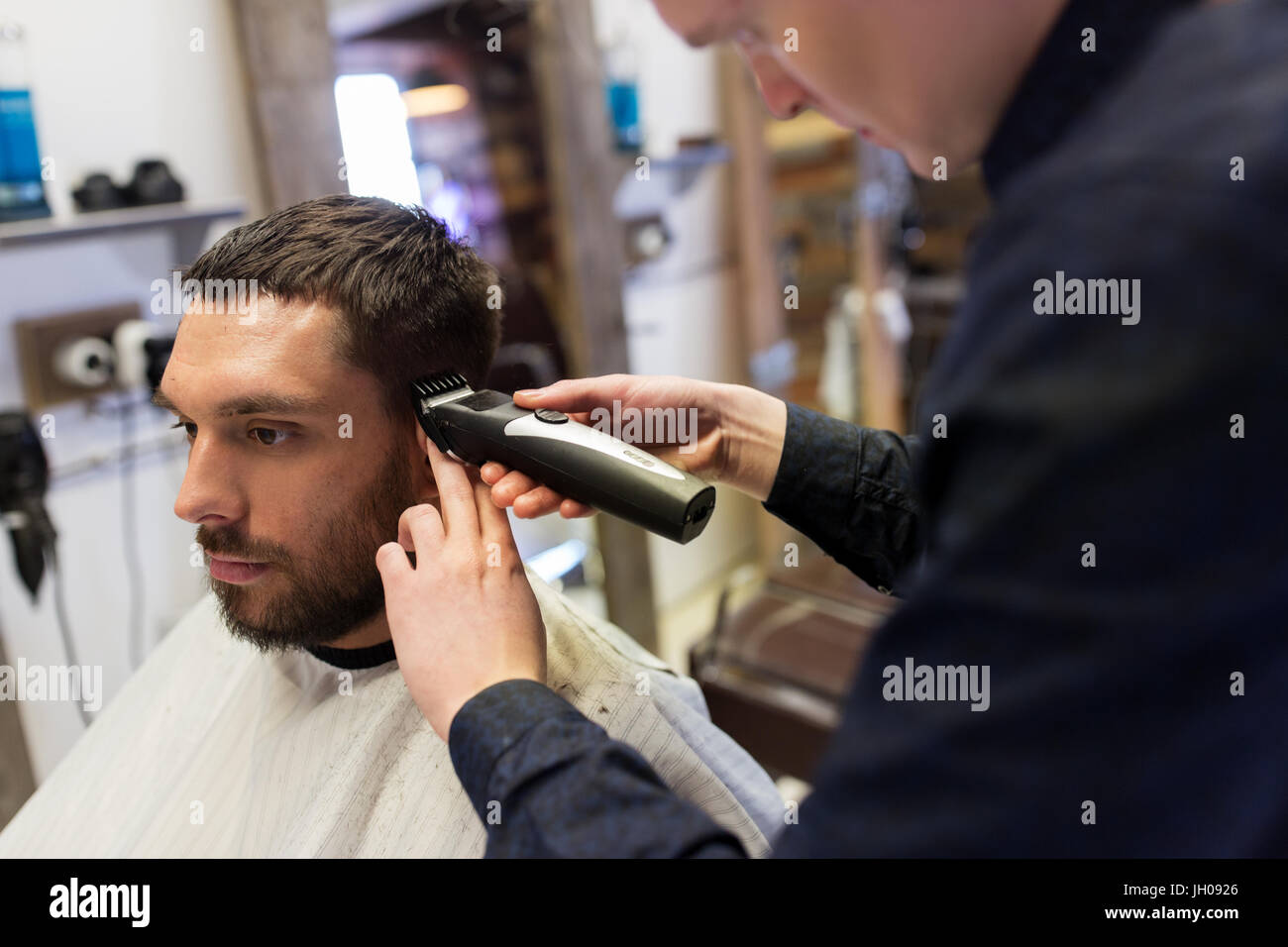 man and barber with trimmer cutting hair at salon - Stock Image