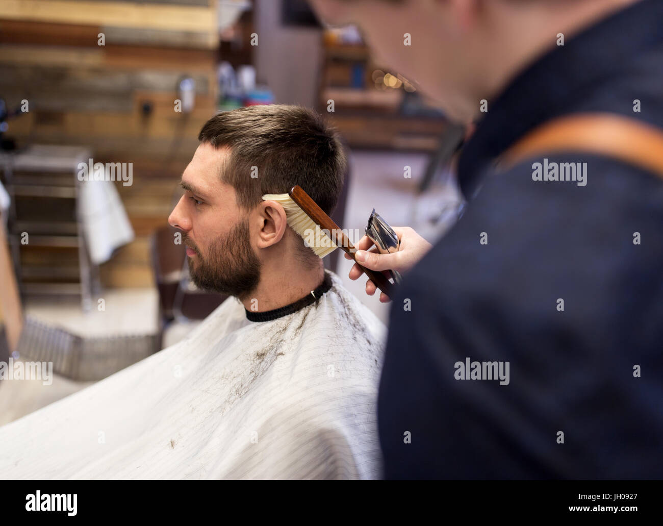 man and barber with brush cleaning hair at salon - Stock Image