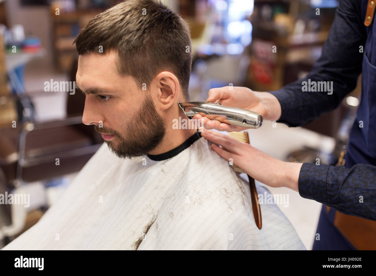 man and barber hands with trimmer cutting hair - Stock Image