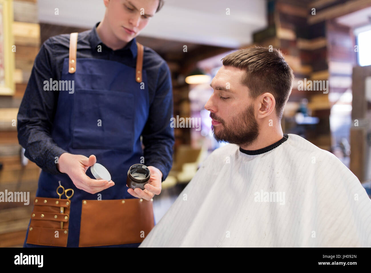 barber showing hair styling wax to male customer - Stock Image
