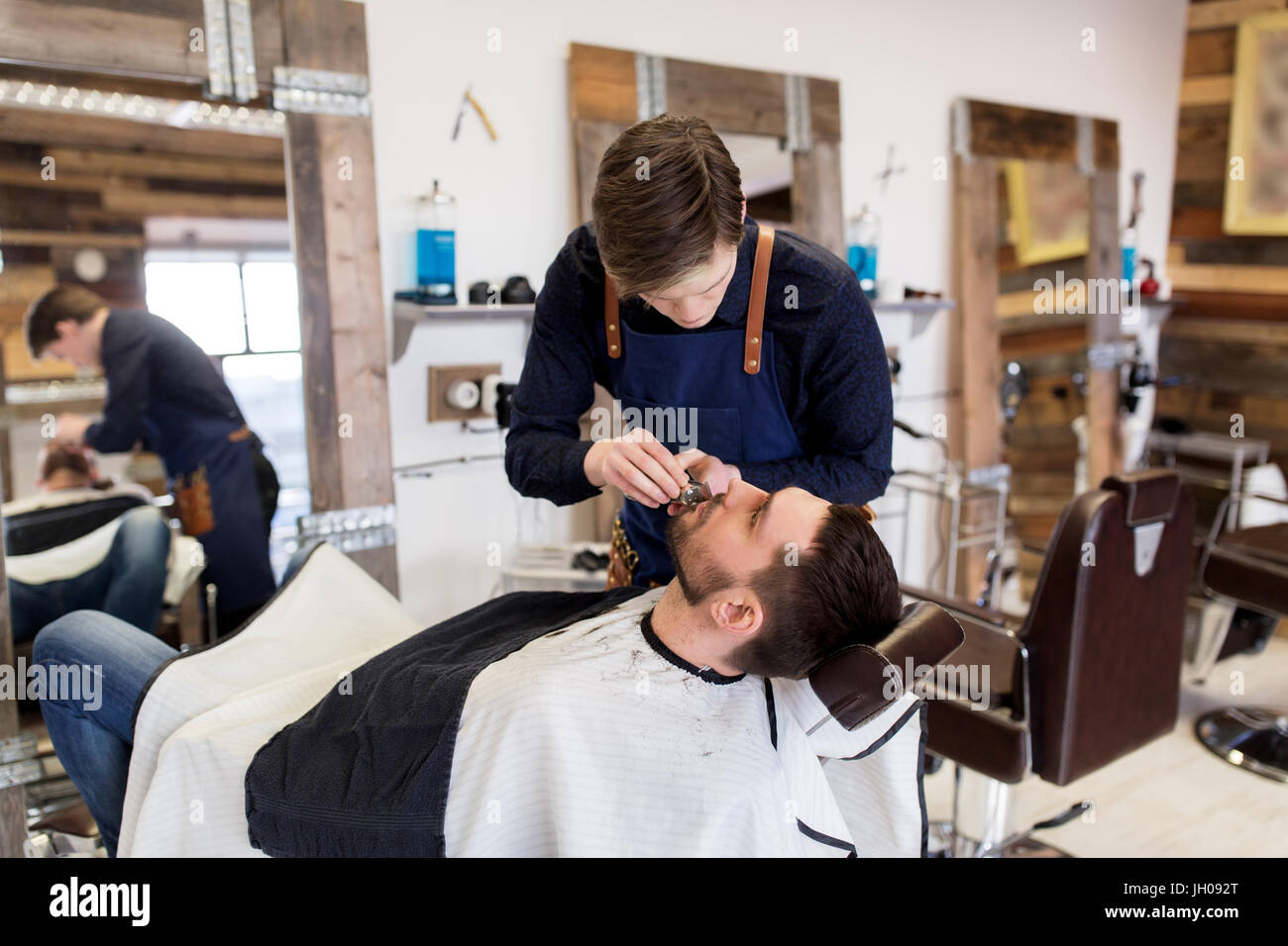 man and barber with trimmer cutting beard at salon - Stock Image