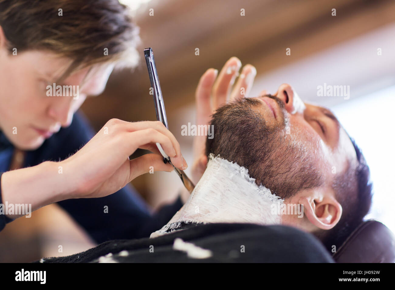 man and barber with straight razor shaving beard - Stock Image