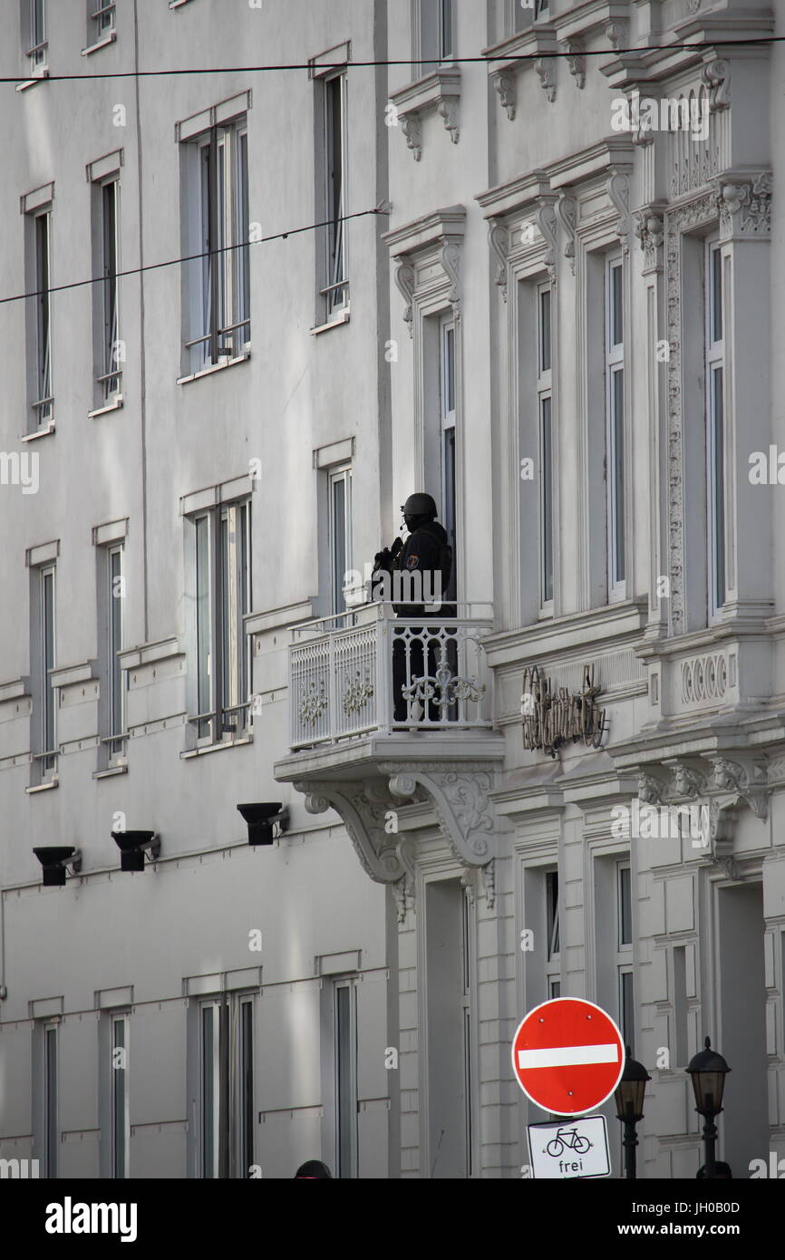 Heavy armed police man on a balcony near the Atlantic Hotel during the G20 summit in Hamburg - Stock Image