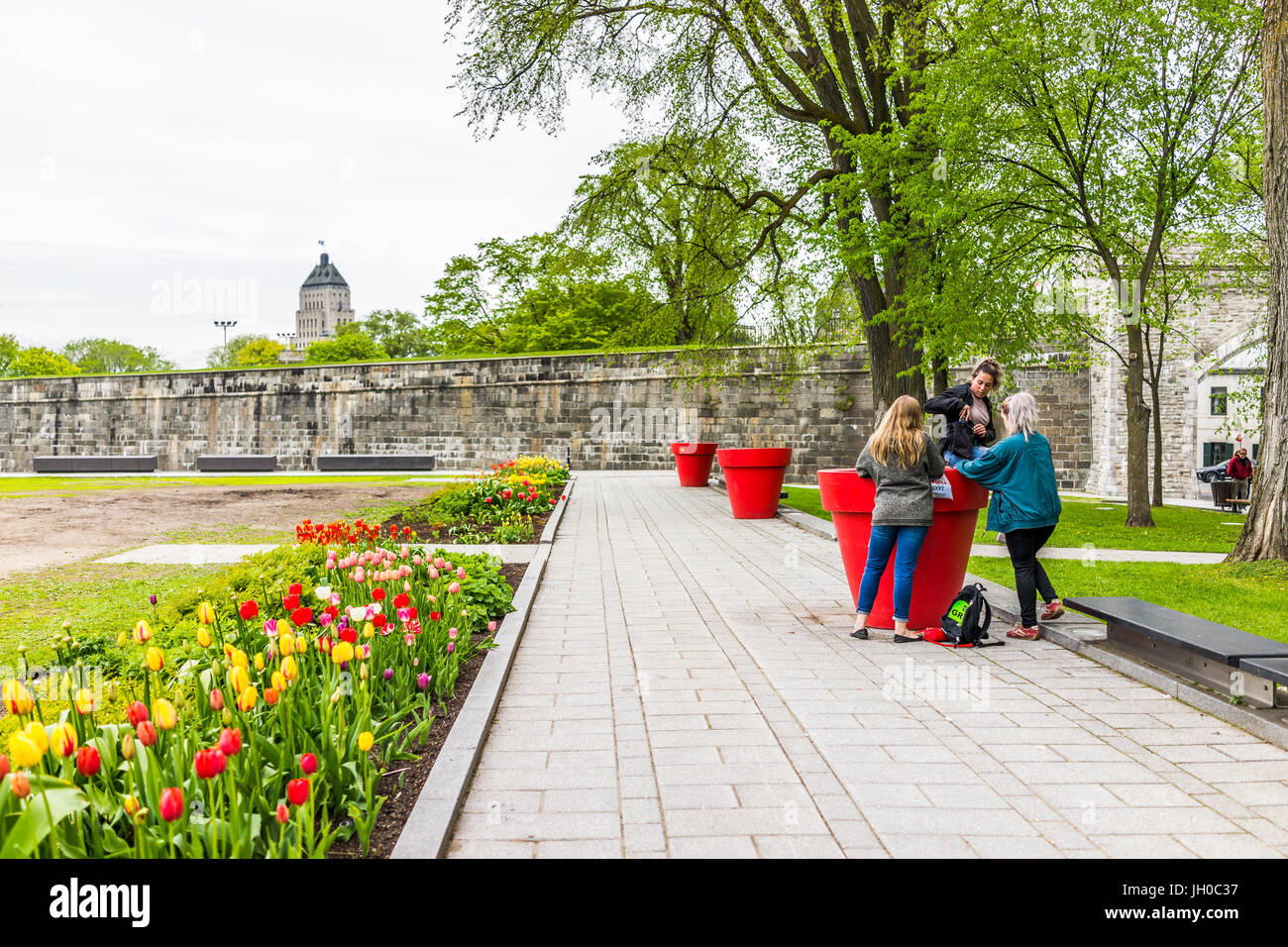 Quebec City, Canada - May 29, 2017: Green grass fields plains in park with fortifications stone wall and people - Stock Image