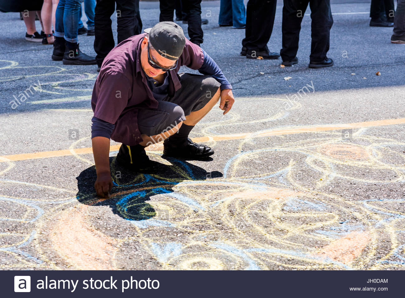 Man creating chalk drawing on road. Balmoral Block Party in support of evicted residents of Downtown Eastside Slum - Stock Image