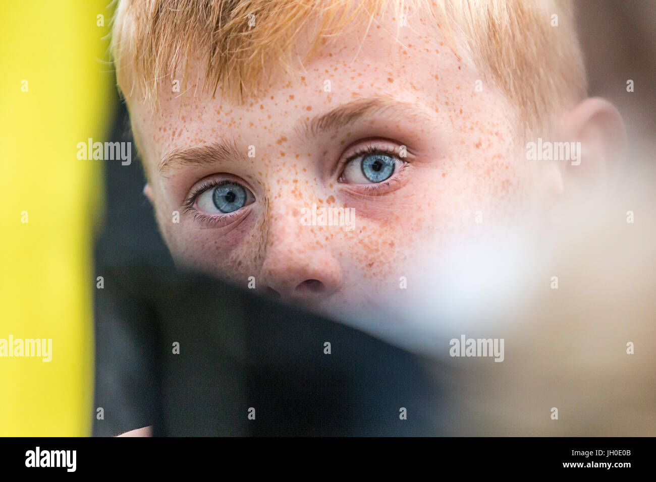 Young blue-eyed boy tries to fool the photographer by hiding behind objects - Stock Image