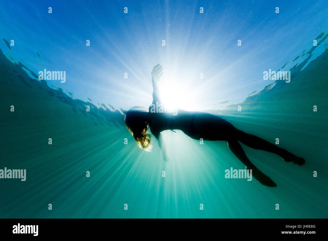 A beautiful woman floats on her back in the ocean as she is surrounded be bright ethereal light and sun rays. Stock Photo