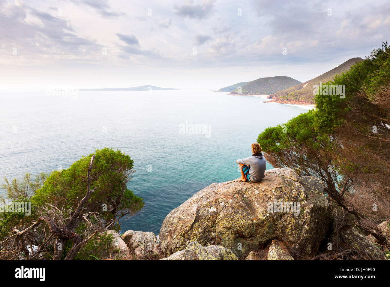 A man sits on a boulder overlooking a panoramic view of a beautiful ocean coastline near Newcastle, Australia. Stock Photo