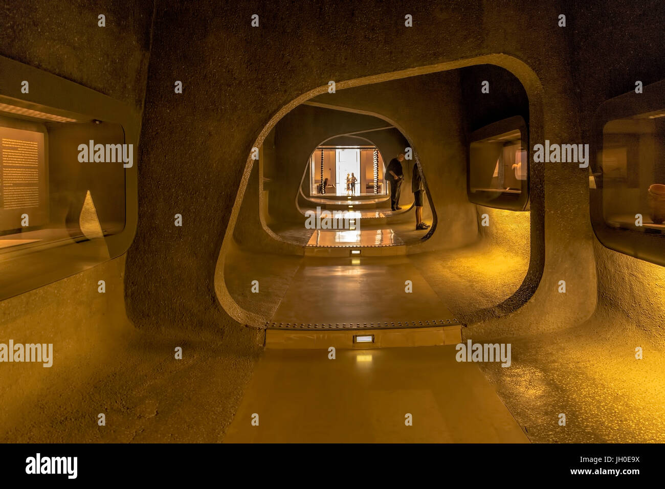 View into a dark cave-like passage with exhibits towards the entrance area of the Israel Museum in Jerusalem, Israel, famous for the Dead Sea Scrolls. Stock Photo