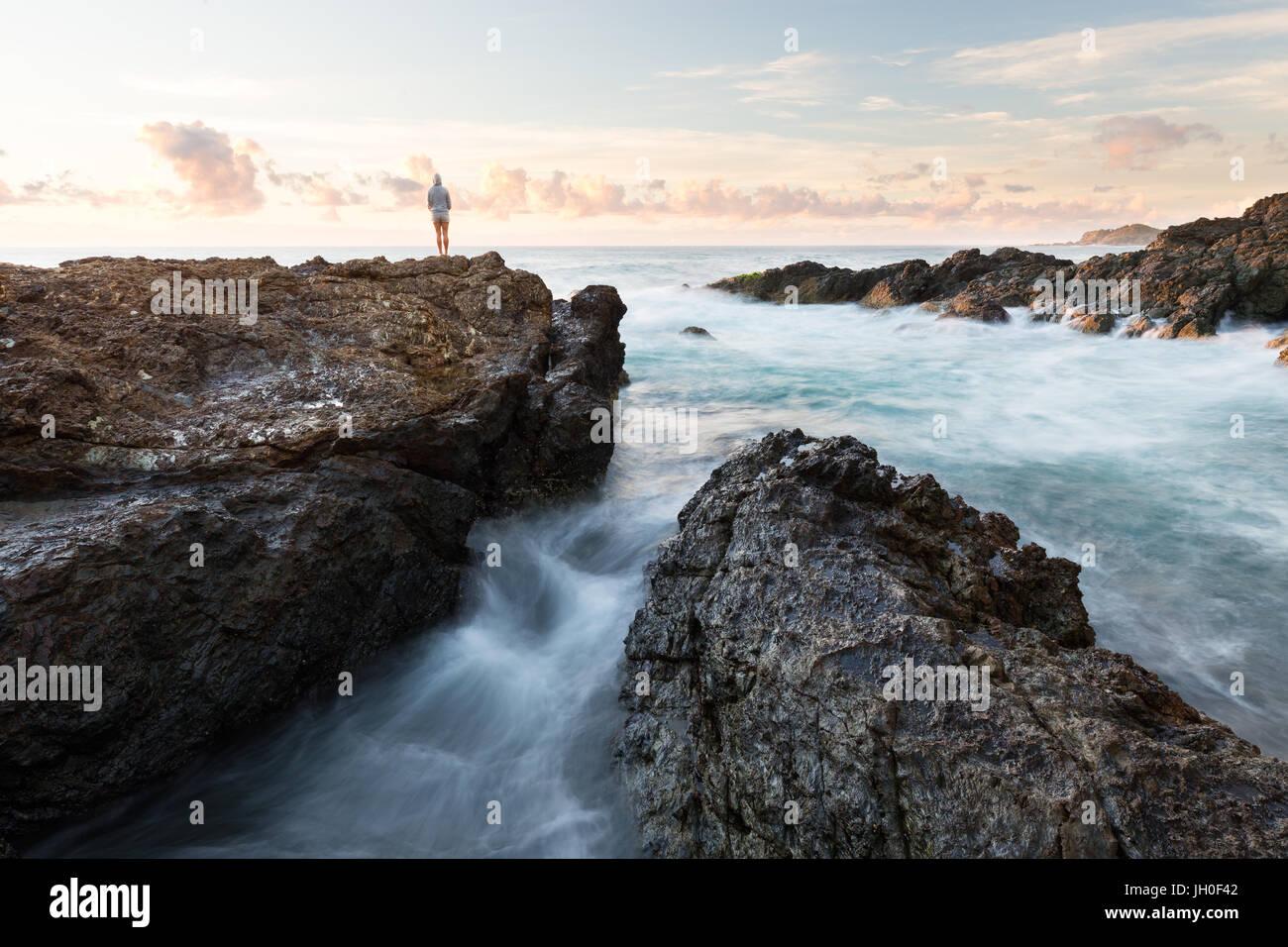 A person watches the sun rise over the ocean in a beautiful rocky seascape scene in Port Macquarie, Australia. - Stock Image
