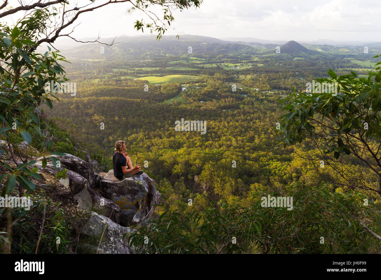 A young man sits, quietly meditating on top of a mountain with expansive views near Noosa Heads, Australia. - Stock Image